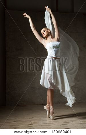 Portrait of blonde ballet dancer with arms up dancing on pointes in studio