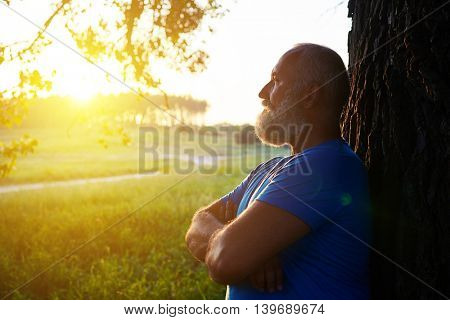 Side view of handsome fit bearded aged man near the tree watching beautiful sunset