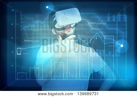 Young bearded man in virtual reality glasses is looking at the digital display with graph and thinking about the data
