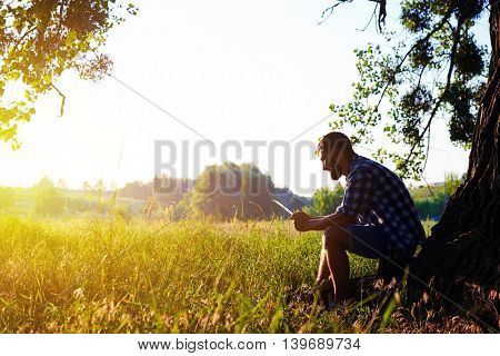 Young man is sitting beneath a tree with his data tablet on the background of beautiful summer sunset in the field