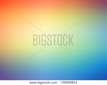 Abstract gradient rainbow orange blue yellow green colored blurred background.