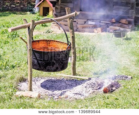 Empty cast iron pot hung above hot smoking coals