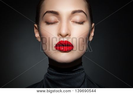 Young model with eyes closed and red lips on black background