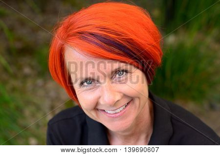 Attractive sincere smiling redhead woman looking intently at the camera with a lovely friendly smile close up head and shoulders outdoors against greenery