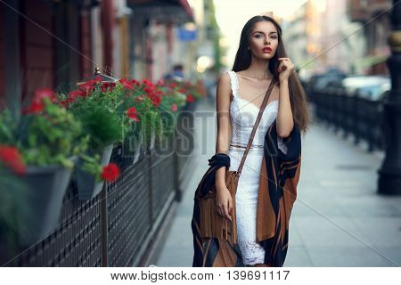 Young sexy beautiful pretty woman in white elegant dress and cape walking at city street with handbag. Fashion portrait of stylish trendy girl with shallow DOF