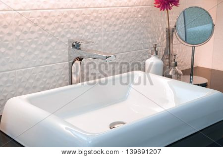 faucet with white wash basin with ceramic tile background