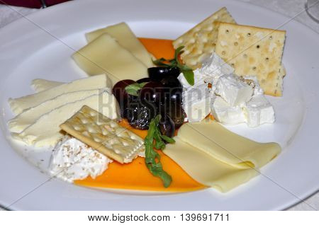 Food on a plate delicatessen cheese, bread, olives, cheese and grapes