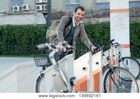 Man Taking A Bike In A Bike Sharing City Service
