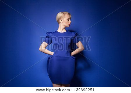 Studio shot of young blonde girl with short hair in blue dress posing against of blue background.Isolate