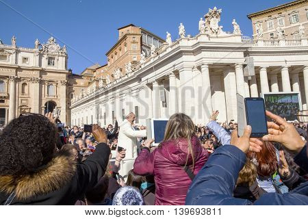 VATICAN,ROME - MARCH 01, 2016: Pope Francis I on the popemobile blesses the faithful crowd in St. Peter's Square in Vatican on March 01, 2016.