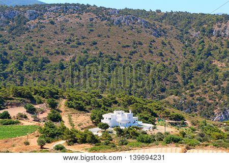 Summer mountain landscape with white villa among the green vegetation.