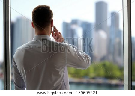 business people and office concept - businessman calling on smart phone over office near with window