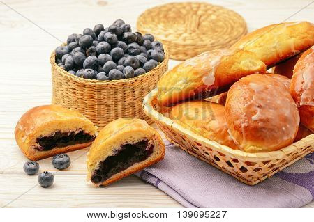 Blueberry filled yeast buns on white table.