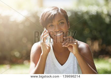 Portrait Of Charming African Female With Short Hairstyle Sitting On The Grass, Talking On Mobile Pho