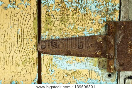 Rustic paint on a wooden plank and door hinge