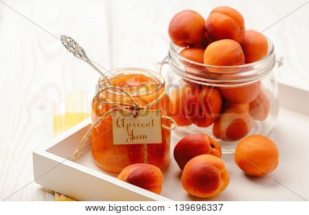 Apricot jam in glass jar on white tray.