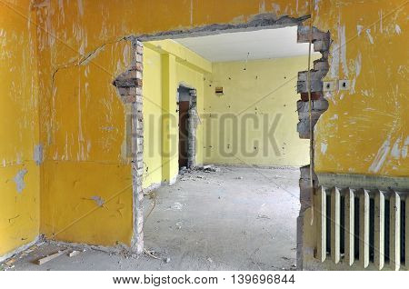 The process of repair reconstruction of the building. Peeled yellow wall gray concrete floor and broken doorways.