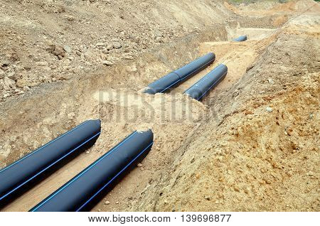 The process of laying of engineering and heating systems. Two black plastic pipes are in a trench of sand in perspective.
