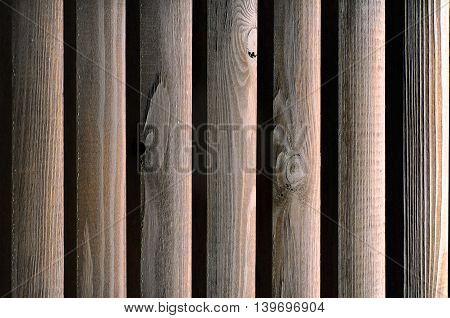 Texture of wooden boards brown illuminated from the back side. Shutters closeup.