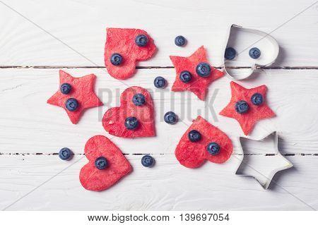 Watermelon hearts & stars on wooden background . Dessert .