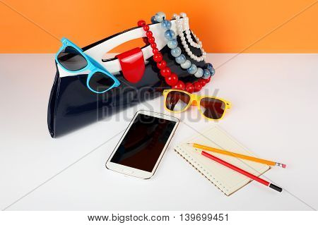Women's Fashion Accessories. Your style - sunglasses handbag phone and notebook are decorated with a beads and a pearl necklace.
