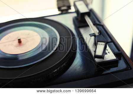 Sound recording and reproduction - The vintage player of vinyl records with a retro toning