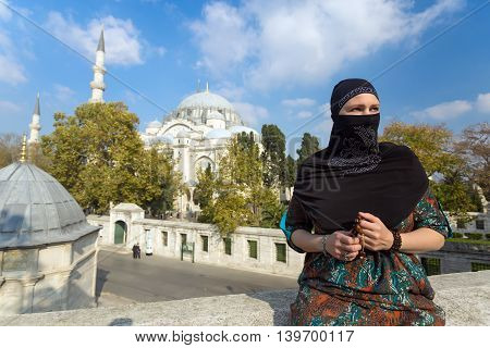 Portrait of beautiful Arabian Woman in traditional Muslim Clothing Middle East Urban landscape with Mosque and Minarets on Background
