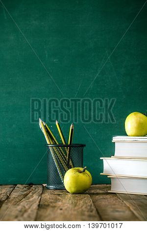 Back to school. School background with supplies. Pencils apple and school equipment.