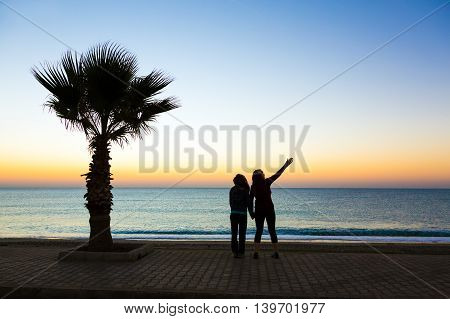 Two people enjoying sunrise sea view at seafront promenade at Mediterranean tropical location Palm Tree