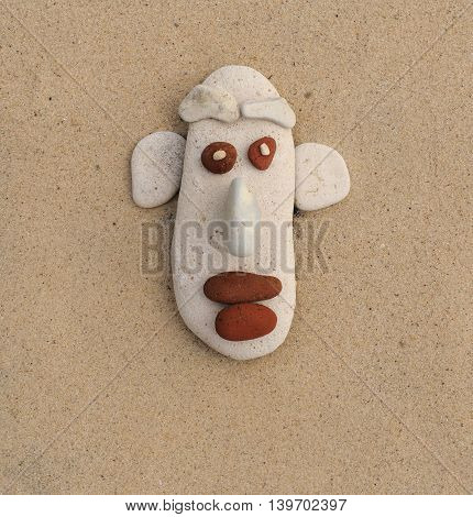 the face of the pebbles on the sand. caricature and humor for greeting cards.