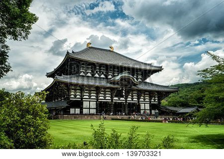 Nara - July 2016: Todai-ji Temple with visitors, surrounding greenery and dynamic clouds.