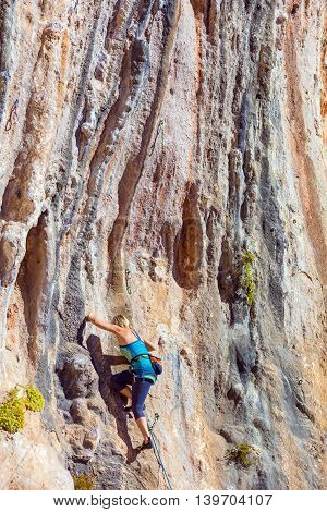 Blond Female Climber ascending Vertical Orange Rocky Wall unusual shape of Mountain Range on background Outdoor Sunshine