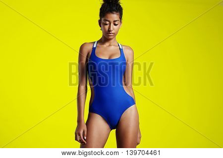 contrast portrait on woman in swimsuit on a yellow wall