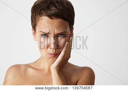 woman with a teeth pain holding her cheek