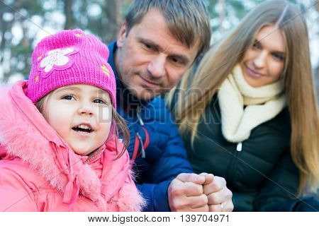 Young Family smart Father beautiful Mother little Baby Daughter together smiling outdoor Portrait