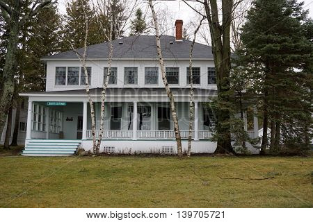 WEQUENTONSING, MICHIGAN / UNITED STATES - DECEMBER 23, 2015: White birch trees (Betula papyrifera) stand in front of a Wequetonsing home, christened Burt Cottage, on Beach Drive.