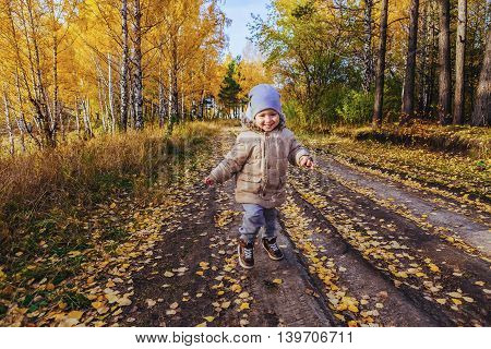 Boy running on the road in the autumn forest yellow leaves on the trees and the road track birch and spruce