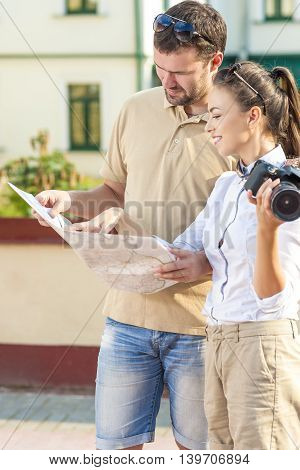 Travel and Vacations Concepts. Happy Young Couple Traveling Together. Exploring City Map in City. Vertical Image Orientation