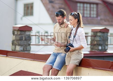 Travel and Vacations Concepts. Happy Young Couple Traveling Together. Exploring City Map in City. Horizontal Image Orientation