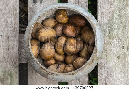 Pot with boiled potatoes in their skins rustic food the pot on the boards the food is cooked on an open fire.