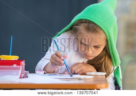 Girl Enthusiastically Paints Watercolors Sitting At A Table In The Yard
