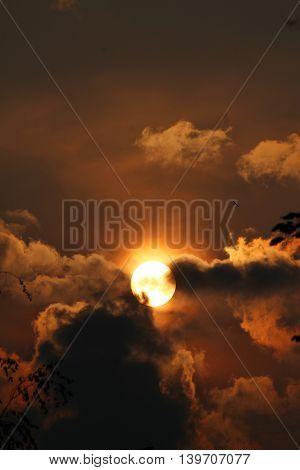 beautiful summer sunset golden disk of the sun into dark clouds