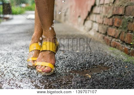 Women's legs under the raindrops puddles and splashing water rain. Summer day yellow sandals