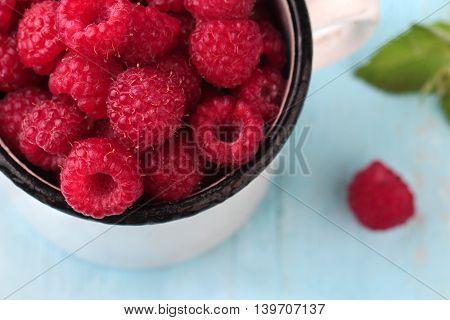 Raspberries in a enamel mug on blue wooden background. Top view.