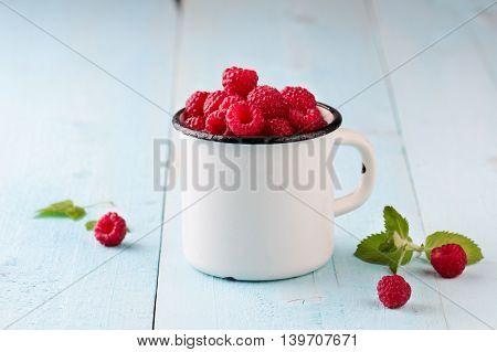 Raspberries in a enamel mug on blue wooden background.