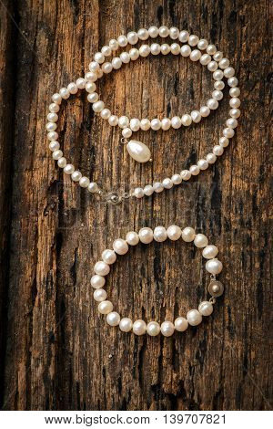 White pearl put on old wooden table.