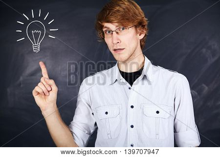 pensive young man with glasses pointing finger up on the background of the board