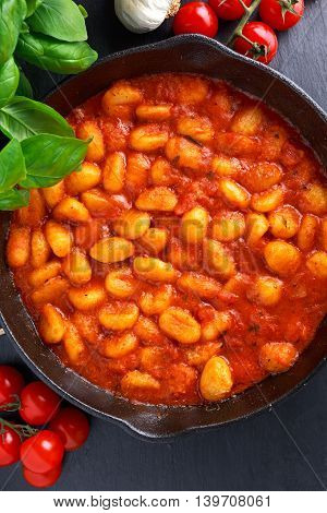 Homemade Italian Gnocchi with marinara sauce in iron pan.