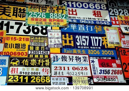 Hong Kong China - December 11 2006: Advertising cards for apartment rentals and businesses covers a wall on a street in Kowloon's Mongkok district