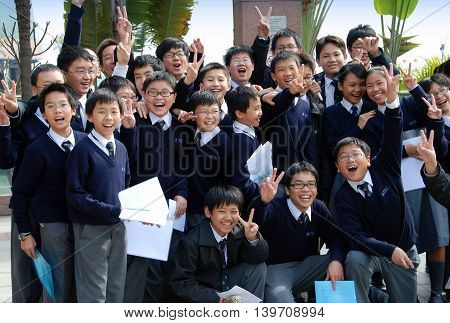 Hong Kong China - January 22 2007: A group of school children pose for their teacher's camera on the Avenue of the Stars in Kowloon